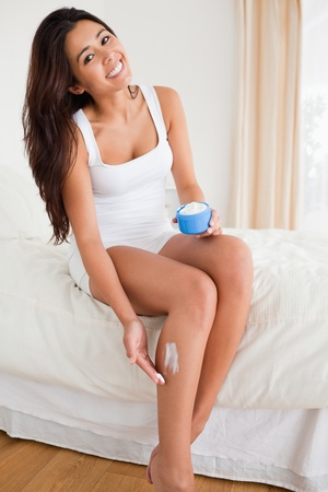beautiful woman putting creme on her legs while sitting on bed in bedroom photo