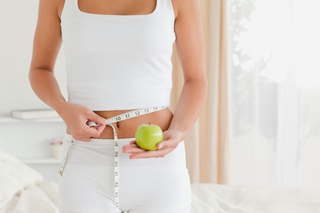 pretty woman measuring her waist while holding an apple in bedroom photo