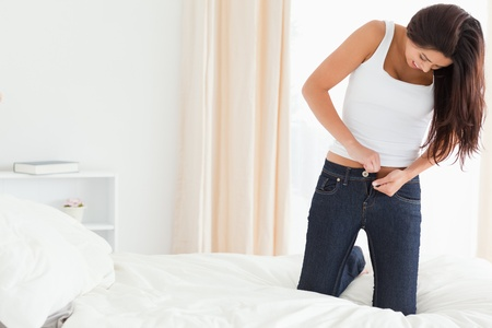 brunette woman kneeing on bed trying to close her jeans in bedroom photo