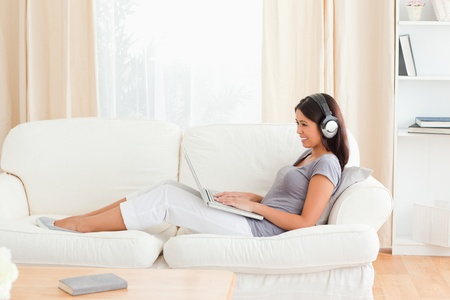 charming woman with earphones sitting on sofa in livingroom photo