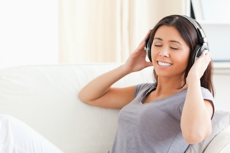 lovely woman with earphones and closed eyes sitting in livingroom photo