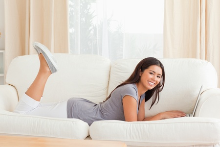 charming woman lying on sofa with notebook in front of her smiling into camera in livingroom photo