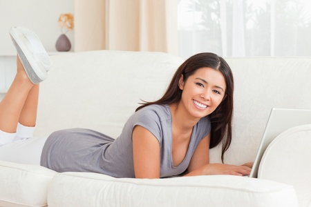 cute woman lying on sofa with notebook in front of her smiling into camera in livingroom photo