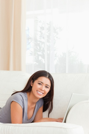 beautiful woman lying on sofa with notebook in front of her smiling into camera in livingroom photo