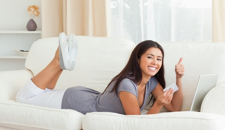 smiling woman with thumb up and card in hand lying on sofa in livingroom looking into camera photo