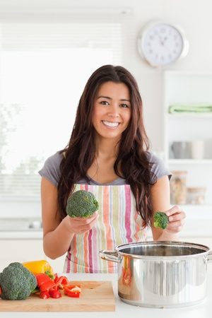 Attractive female preparing vegetables while standing in the kitchen photo