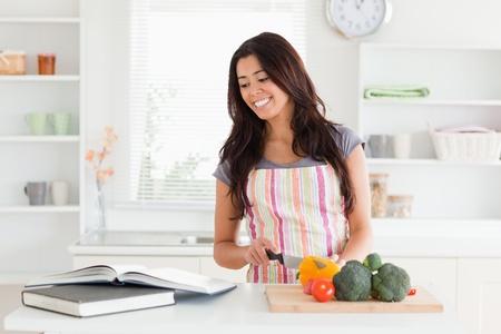 cuchillo de cocina: Hermosa mujer de consultar a un port�til mientras que cocinar las verduras en la cocina