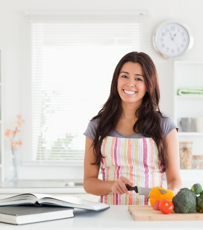 Charming woman consulting a notebook while cooking vegetables in the kitchen photo