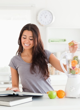 Attractive woman consulting a notebook while filling a blender with fruits in the kitchen photo