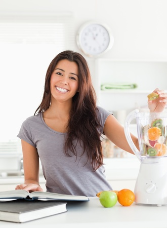 Good looking woman consulting a notebook while filling a blender with fruits in the kitchen photo
