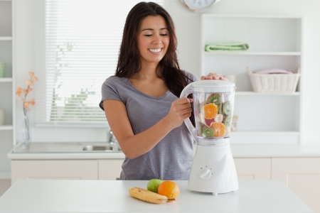 Charming woman using a blender while standing in the kitchen photo