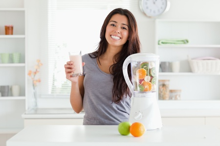 Beautiful woman using a blender while holding a drink in the kitchen photo