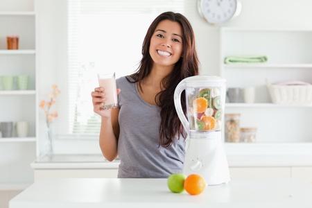 licuadora: Hermosa mujer con una batidora, mientras sostiene una copa en la cocina