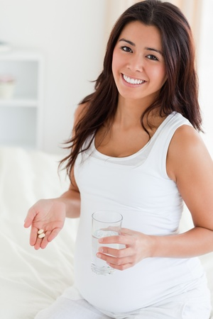 Attractive pregnant woman holding a glass of water and pills while sitting on a bed at home photo