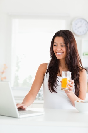 Gorgeous woman relaxing with her laptop while holding a glass of orange juice in the kitchen photo
