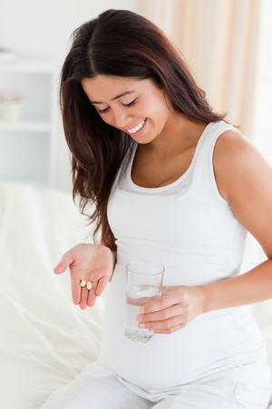 new medicine: Good looking pregnant woman holding a glass of water and pills while sitting on a bed at home Stock Photo