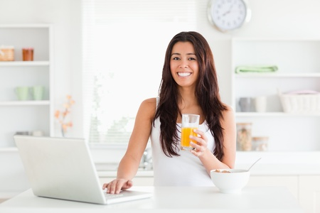 Beautiful woman relaxing with her laptop while holding a glass of orange juice in the kitchen photo