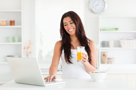 Good looking woman relaxing with her laptop while holding a glass of orange juice in the kitchen photo