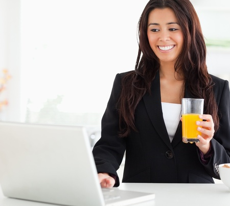 Pretty woman in suit relaxing with her laptop while holding a glass of orange juice in the kitchen photo