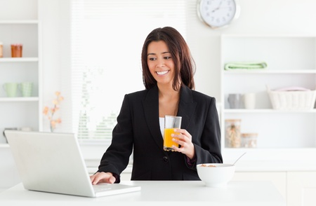 Charming woman in suit relaxing with her laptop while holding a glass of orange juice in the kitchen photo
