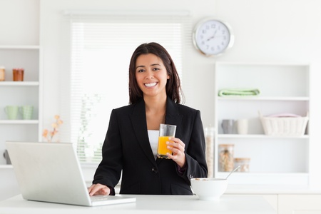Gorgeous woman in suit relaxing with her laptop while holding a glass of orange juice in the kitchen photo