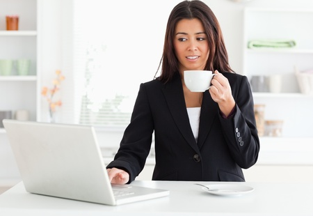 Gorgeous woman in suit enjoying a cup of coffee while relaxing with her laptop in the kitchen photo