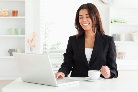 Beautiful woman in suit enjoying a cup of coffee while relaxing with her laptop in the kitchen photo