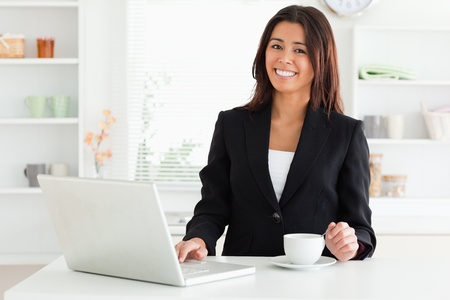 Attractive woman in suit enjoying a cup of coffee while relaxing with her laptop in the kitchen photo