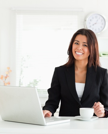 Good looking woman in suit enjoying a cup of coffee while relaxing with her laptop in the kitchen photo