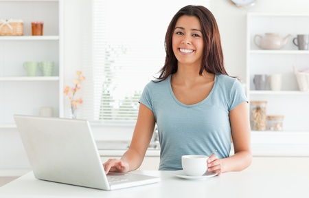 Good looking woman enjoying a cup of coffee while relaxing with her laptop in the kitchen photo