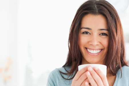 Portrait of an attractive woman enjoying a cup of coffee in the kitchen photo
