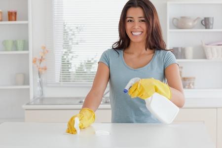 desinfectante: Hermosa mujer haciendo las tareas del hogar mientras se utiliza un spray en la cocina Foto de archivo