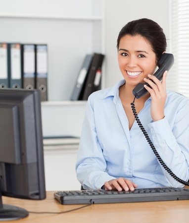 Good looking woman on the phone while typing on a keyboard at the office photo