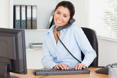 Lovely woman on the phone while typing on a keyboard at the office Stock Photo - 11205392