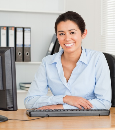 Beautiful woman posing while sitting at the office photo