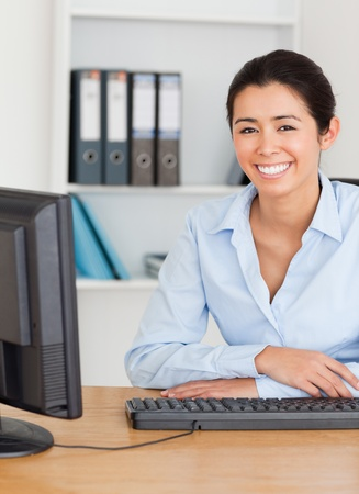 Charming woman posing while sitting at the office photo