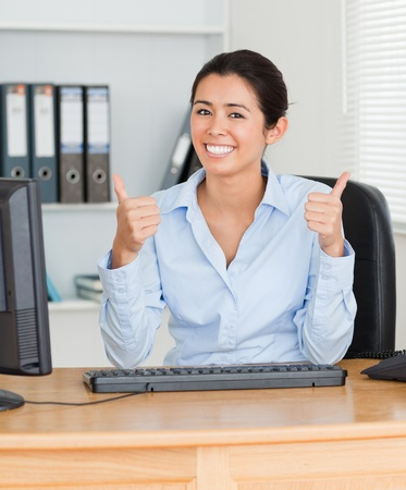 Proud beautiful woman with thumbs up posing while sitting at the office photo