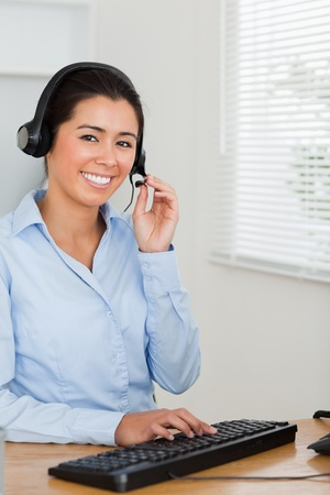 Attractive woman with a headset helping customers while sitting at the office photo