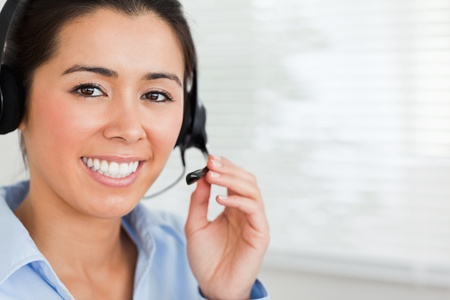 Portrait of a beautiful woman with a headset helping customers while sitting at the office photo