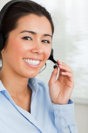 Portrait of a good looking woman with a headset helping customers while sitting at the office photo