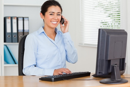 Beautiful woman using her mobile phone while typing on a keyboard at the office Stock Photo - 11205729