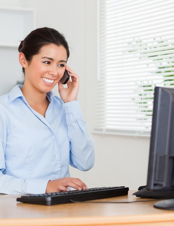 Charming woman using her mobile phone while typing on a keyboard at the office Stock Photo - 11199614