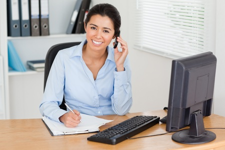 support desk: Charming woman using her mobile phone while writing on a sheet of paper at the office