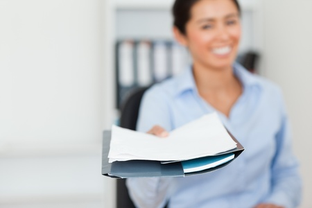 Good looking woman showing a sheet of paper to the camera at the office photo