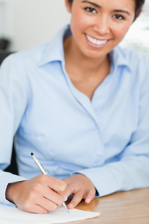 Frontal view of a charming woman writing on a sheet of paper while sitting at the office photo