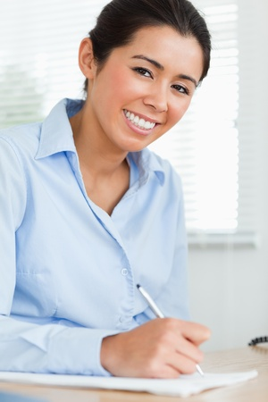 Good looking woman writing on a sheet of paper while sitting at the office photo
