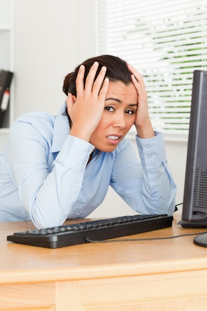 Pretty upset woman looking at a computer screen while sitting at the office photo