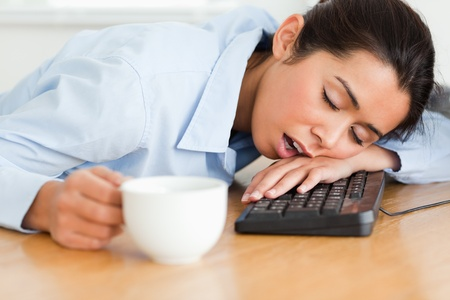 Pretty woman sleeping on a keyboard while holding a cup of coffee at the office photo