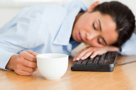 Beautiful woman sleeping on a keyboard while holding a cup of coffee at the office photo