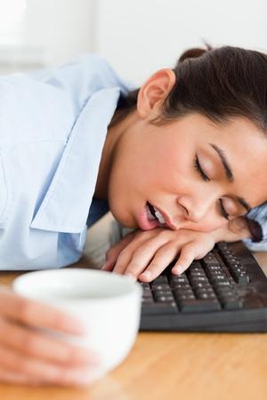 durmiendo: Buena mujer busca dormir en el teclado mientras sostiene una taza de caf� en la oficina